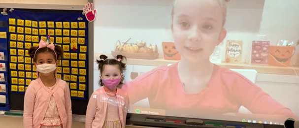 Two elementary girls dress as twins in pink next to projector screen with friend from home dressed the same.