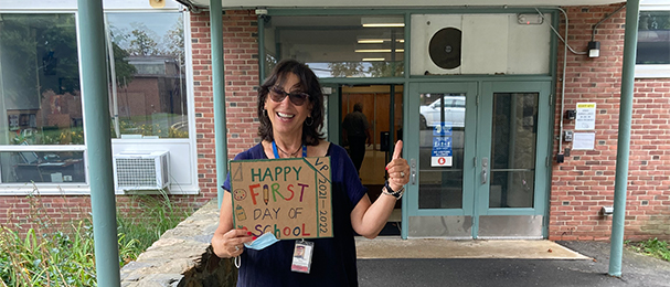 Ms Tuckner with sign saying first day of school