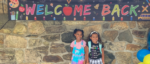 Two young girls standing in front of welcome back sign