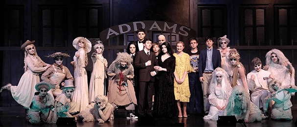 Students in the cast of The Addams Family pose in costume on stage
