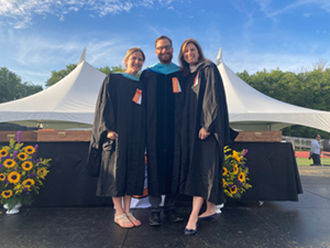 Three teachers in graduation robes