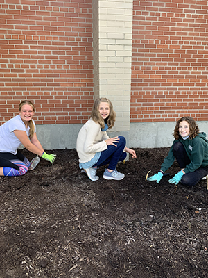 Three happy girls in sixth grade outside planting bulbs