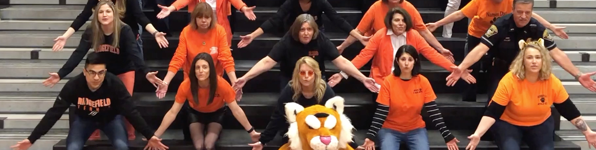 staff on bleachers with the Tiger