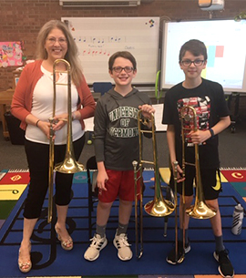 Two students and a staff member pose with instruments