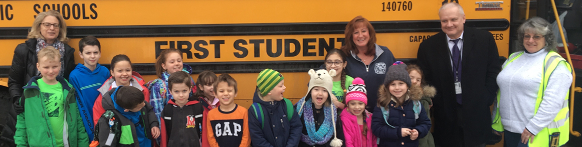 staff members and students in front of bus