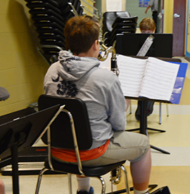 Student musician reads music and sits with his instrument