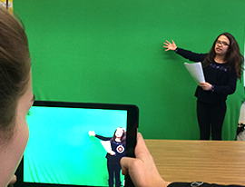 Student giving a presentation in front of a green screen as another student films using a tablet