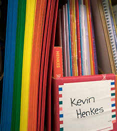 Box with the name Kevin Henkes on it and colorful papers and folders