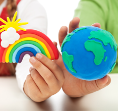Students holding a clay globe and rainbow