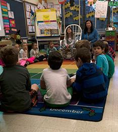 Students and teacher sit on a classroom floor
