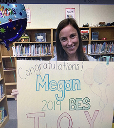 Teacher of the Year holding a Congratulations poster