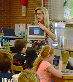 Teacher showing laptops to students
