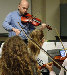Teacher playing a violin as students watch and hold their own violins