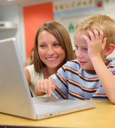 Teacher helps a student using a laptop