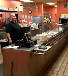 Smiling adult poses behind the cafeteria cash register