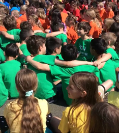 students enjoying a sing along with their arms around each other