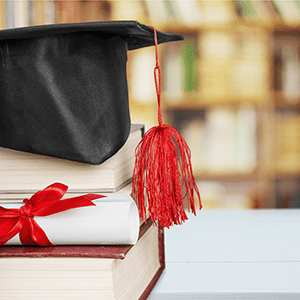 Mortar board with tassel sits on top of stacked books next to a diploma