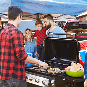 Family stands in front of a man cooking on a grill