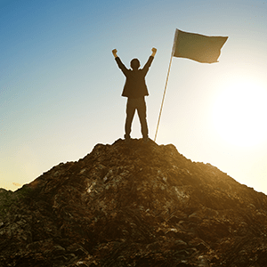 Person cheers as they stand atop a mountain next to a flag