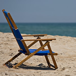 Foldable chair sits on beach sand
