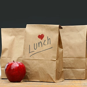 An apple and paper lunch bags with text reading Lunch and a heart