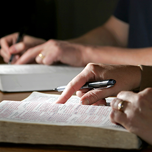 Hands point into an open bible page