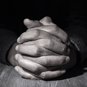 Praying hands placed on top of a wooden surface