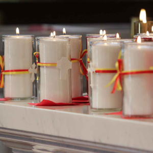 Glowing candles with crosses tied around them sit on a granite surface