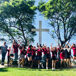 Students jump and pose in front of a cross