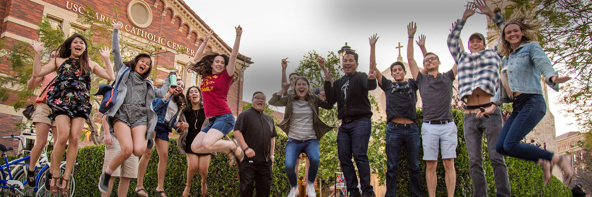 Students jump and pose in front of buildings