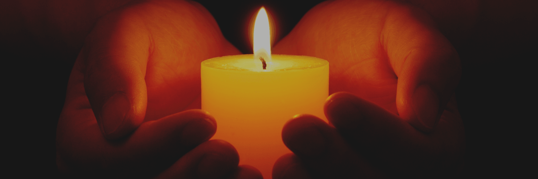 Hands hold a glowing candle