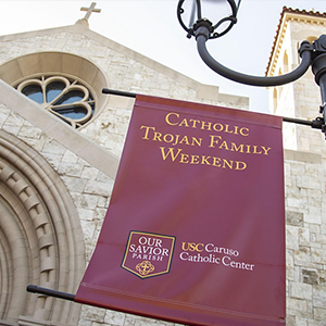 Catholic Trojan Family Weekend sign hanging on a lamppost in front of a building