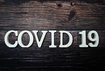 COVID 19 written in blocks on a wood background