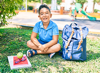 Happy elementary student sitting on grass next to his backpack