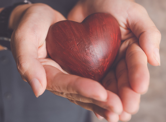 Female hands holding a wooden heart