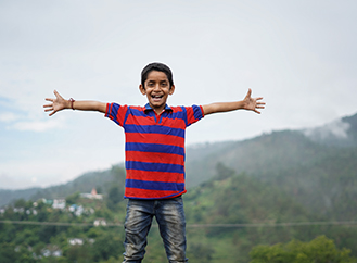 Young boy with arms stretched out in front of a mountain landscape