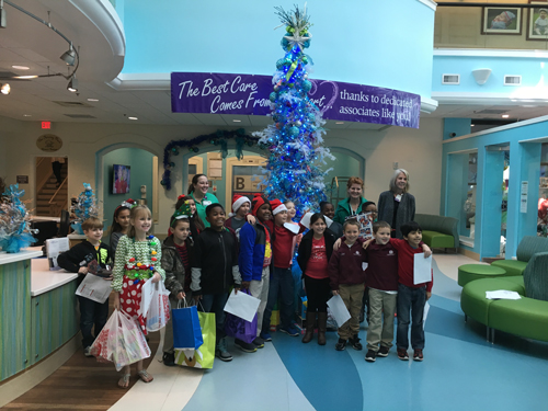 The third grade class at Marcus Pointe Christian School bring gifts to the Sacred Heart Children's Hospital.