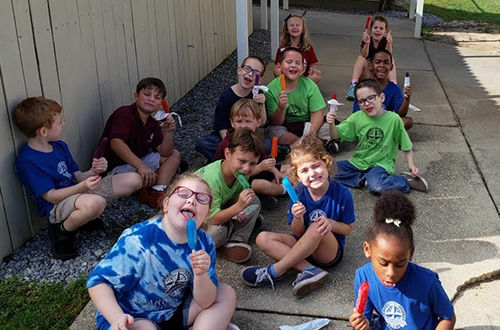 Group of students in blue and green t-shirts enjoying popsicles