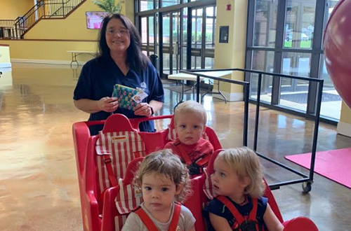 Smiling teacher pushing preschool students in a cart