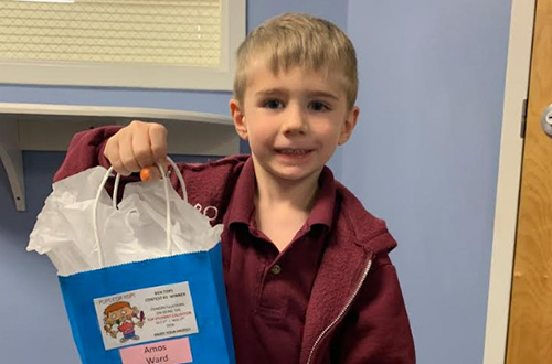 Little boy in maroon shirt holding up a gift bag