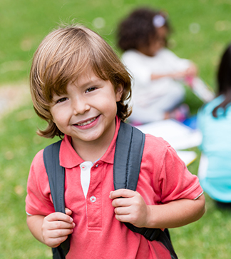 Happy boy with backpack going to preschool