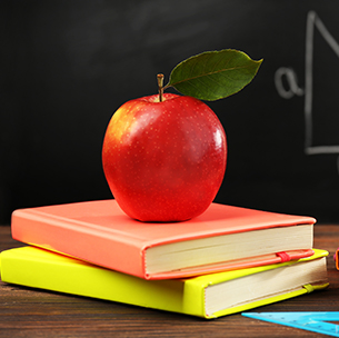 red apple sitting on a stack of books