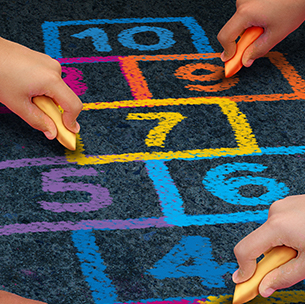 hands drawing hopscotch with sidewalk chalk