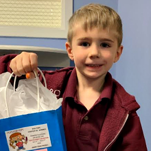 smiling boy with a gift bag in his hand