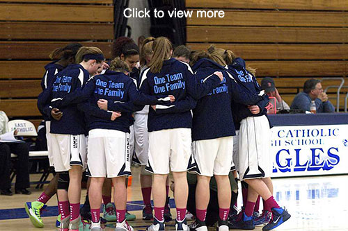 Girls basketball team members huddle in a gym