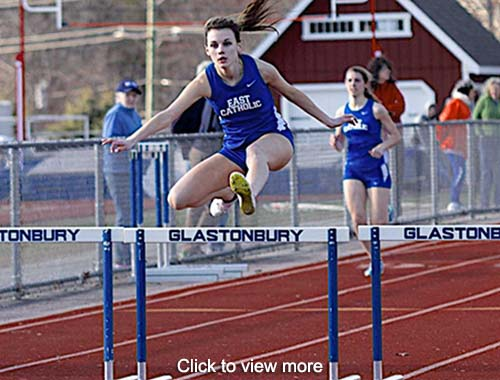 Track and field team member jumps over a barrier