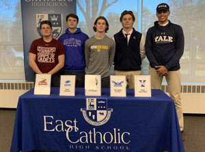 Four students sitting at a college signing table