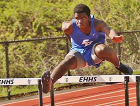 Young man jumping hurdles