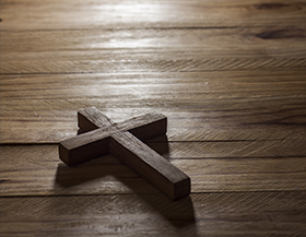 Wooden cross on a wood table