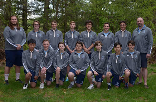 Boys tennis team posing together on grass